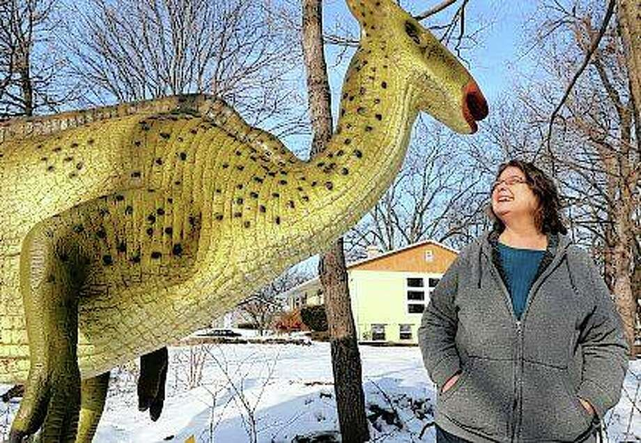 Dolores Graves smiles at her Parasauropholos lawn decoration, named Paris, at her home in DeKalb. Graves, a retired banker, purchased the 8-foot, 230-pound Parasaurolophus statue at a landscape supply store and paid paid $3,000 to buy Paris, and have it taken to DeKalb. Photo: Mark Busch | Daily Chronicle (AP)