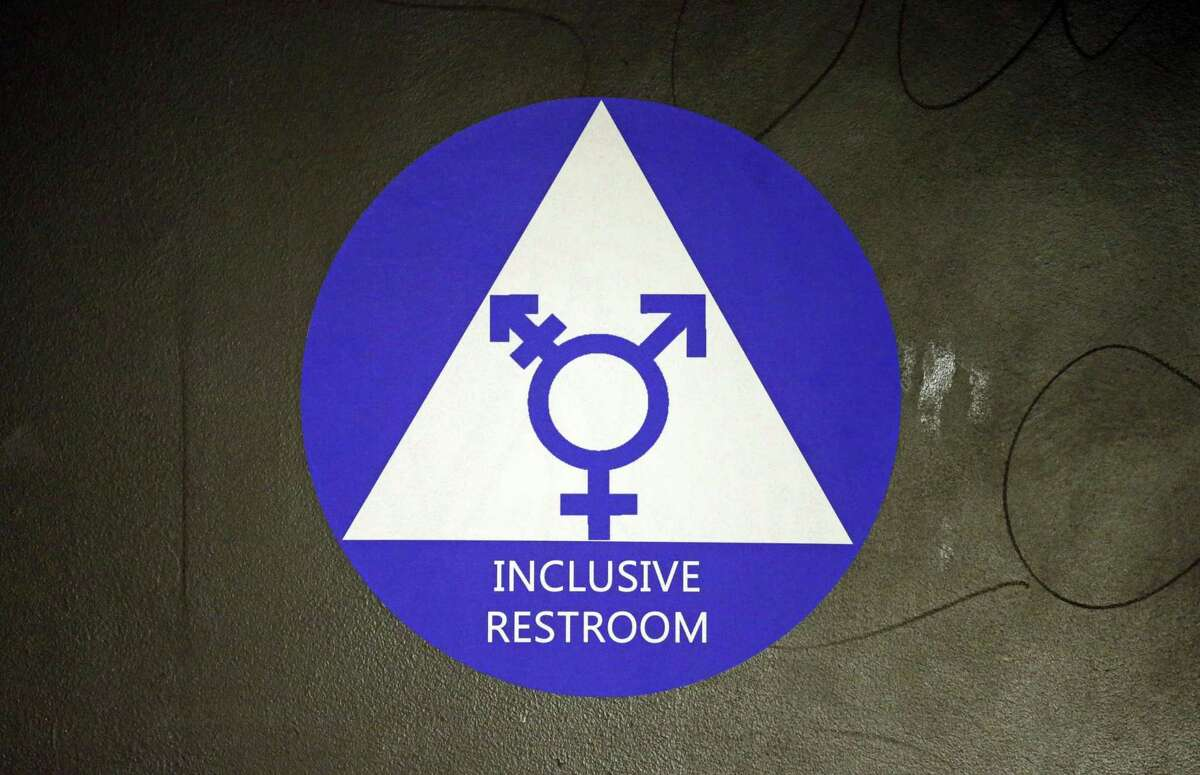 FILE - In this May 17, 2016, file photo, a new sticker designates a gender neutral bathroom in Seattle. A famous spa in Los Angeles' Koreatown became the latest site in the battle over transgender rights last week, (AP Photo/Elaine Thompson, File)