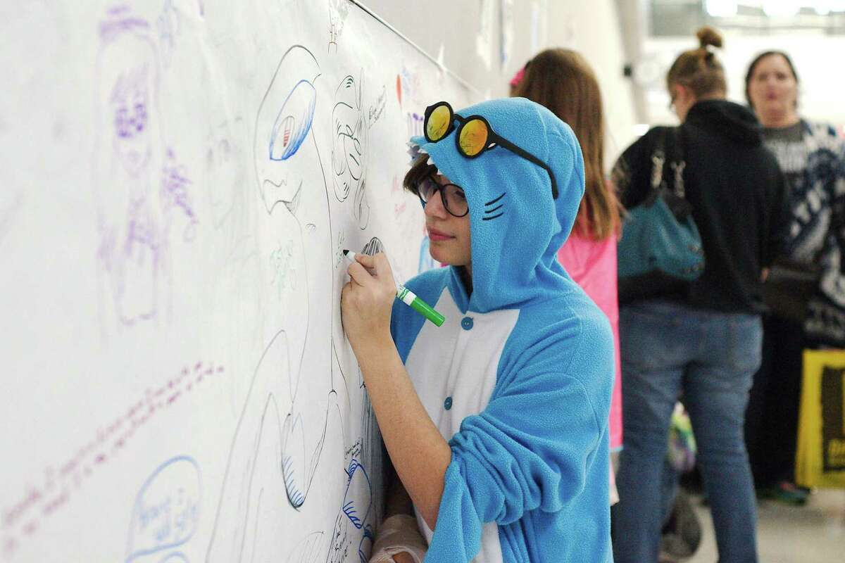 Elise Amaya of Pearland leaves her mark on the graffiti wall at Brazcon Teen Comic Convention Saturday, Feb. 3.