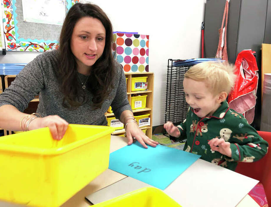 Goshen Elementary School teacher Abby Paustian, left, helps student Hudson Reed with learning letters of the alphabet.