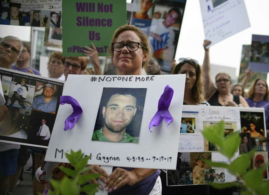 Christine Gagnon, of Southington, Conn., holds a sign during a protest with others who have lost loved ones to OxyContin and Opioid overdoses at the Purdue Pharma headquarters in Stamford, Conn., on Friday, Aug. 17, 2018. Gagnon lost her son Michael 13 months earlier. (AP Photo/Jessica Hill) Photo: Jessica Hill / Associated Press / Copyright 2018 The Associated Press. All rights reserved
