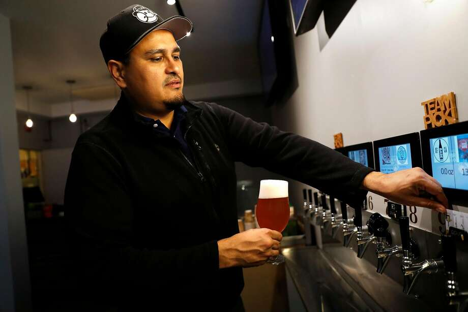 Antonio Mendoza removes his Brew Coop card after pouring an Anderson Valley Cherry Gose at the taproom. Photo: Scott Strazzante / The Chronicle