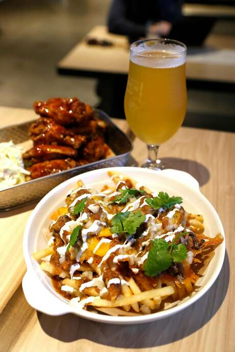 Carne asada fries (foreground), Coop-dobo wings and a Holy Craft Brewing Harajuku Girl rice lager at the Brew Coop on Valencia Street in S.F. Photo: Scott Strazzante / The Chronicle