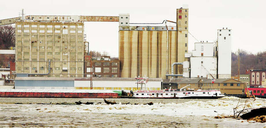 A towboat and barges pushing cargo upriver Monday passes large chunks of ice piled up on the Missouri side of the river, foreground. Below-zero temperatures are expected to move into Illinois this evening and last through Thursday. The National Weather Service said wind chills could reach 55 below zero in northern Illinois, 35 below in central Illinois and 25 below in parts of southern Illinois. Photo: John Badman | The Telegraph