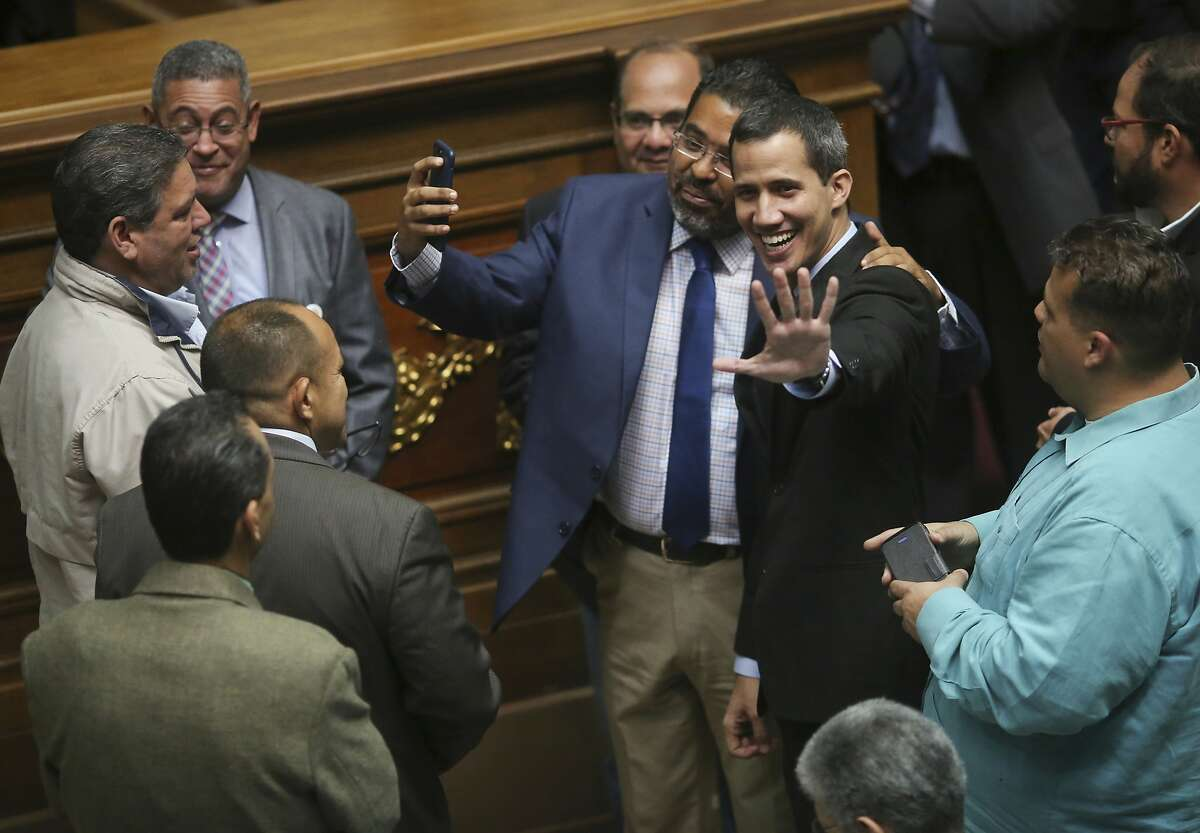 Opposition National Assembly President Juan Guaido, center right, who has declared himself interim president of Venezuela, arrives in the National Assembly, in Caracas, Venezuela, Tuesday, Jan. 29, 2019. Venezuela's chief prosecutor on Tuesday asked the country's top court to ban Guaido from leaving the country, launching a criminal probe into his anti-government activities while international pressure builds against President Nicolas Maduro. (AP Photo/Rodrigo Abd)