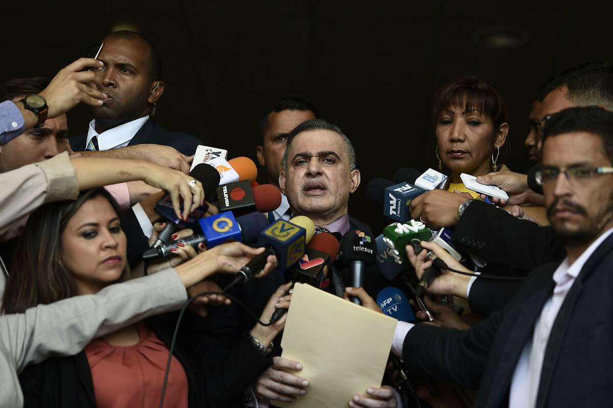 """Venezuelan Prosecutor Tarek William Saab (C), delivers a statement at the Supreme Court of Justice in Caracas to announce he has barred Venezuela's National Assembly head and self-proclaimed """"acting president"""" Juan Guaido, from leaving Venezuela and has freezed his assets, on January 29, 2019. (Photo by Federico Parra / AFP)FEDERICO PARRA/AFP/Getty Images"""