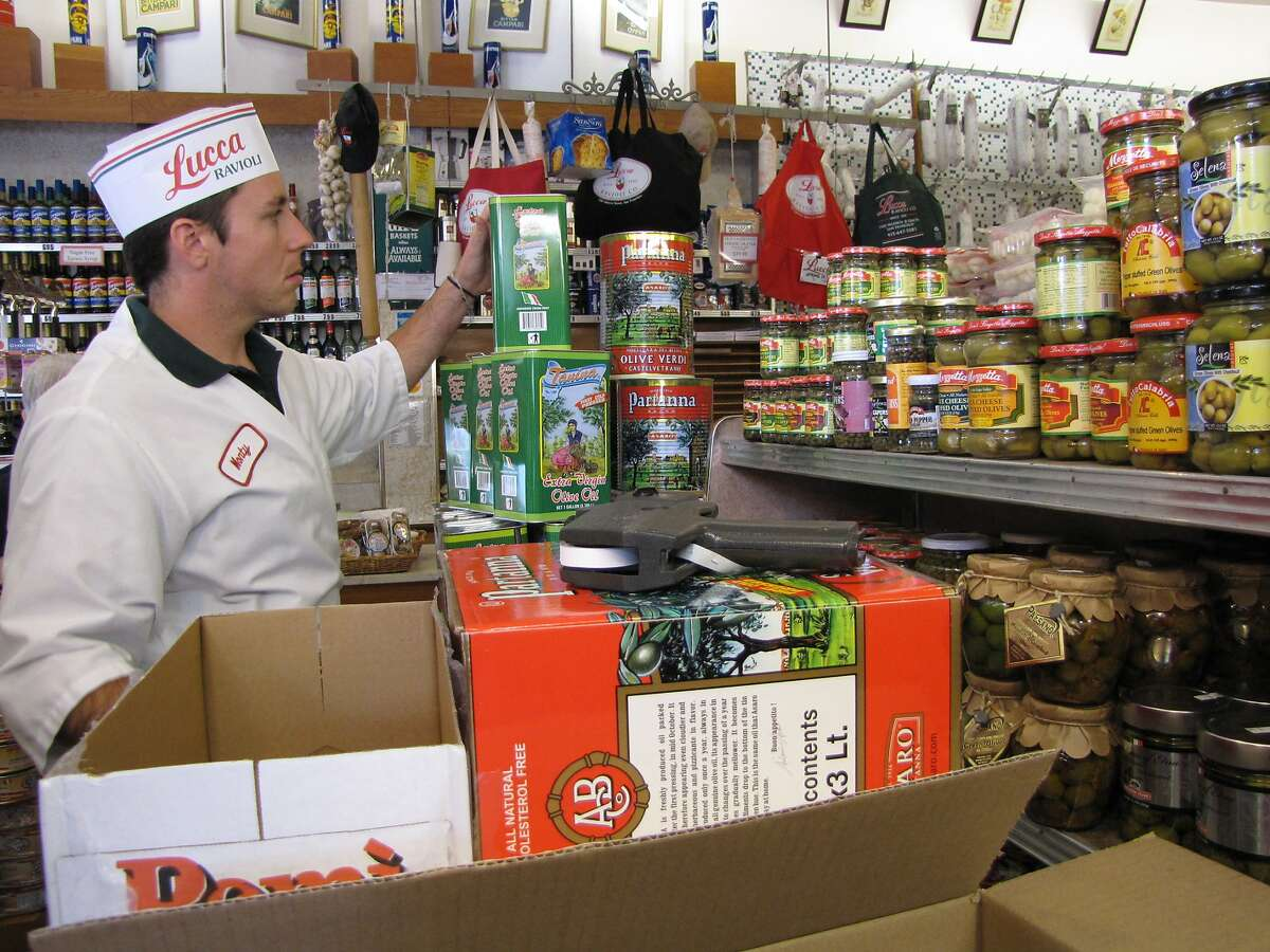 Monty Dobitz stacks containers of Italian olive oil at Lucca Ravioli Company in San Francisco.