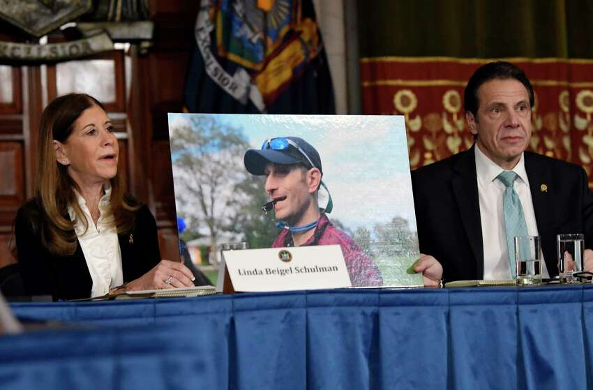 Linda Beigel Schulman, left, holds a photograph of her son Scott Beigel, who was killed by gun violence, while speaking with New York Gov. Andrew Cuomo and gun safety advocates in the Red Room during a news conference at the state Capitol on Tuesday, Jan. 29, 2019, in Albany, N.Y.