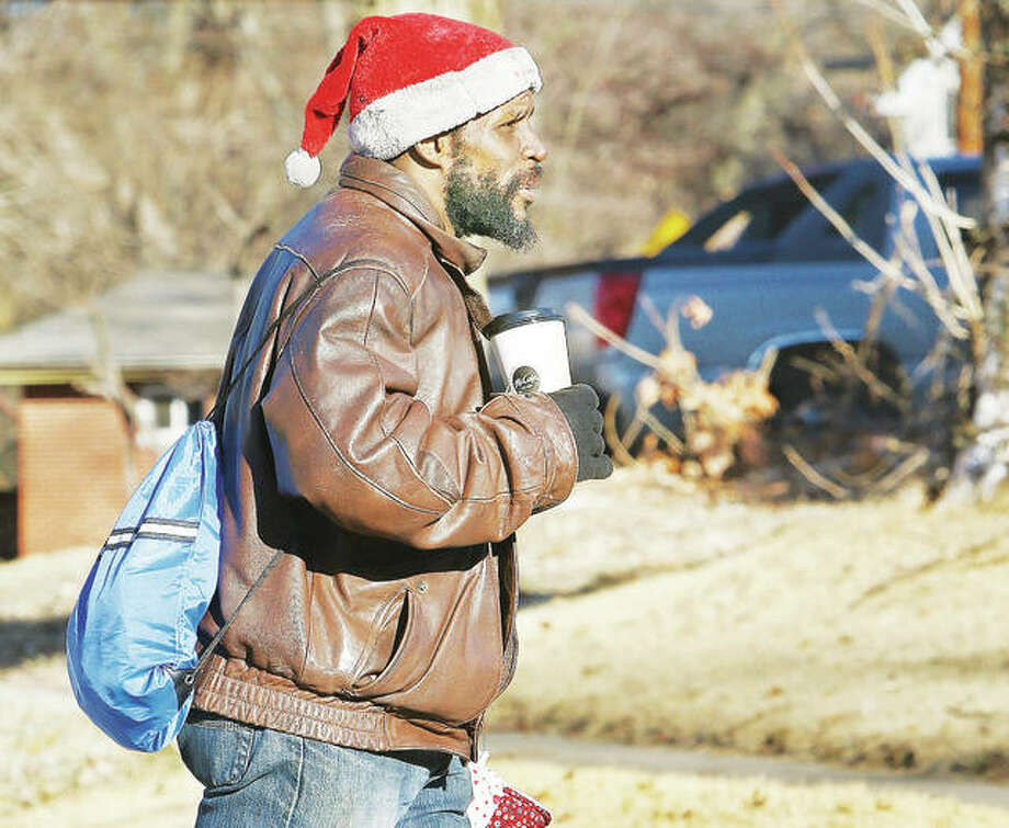 "While many people were staying in Tuesday morning, at least one man was braving the cold with a cup of hot coffee and a Santa Claus hat as he walked up Washington Avenue in Alton. Many area schools called off this morning as a ""polar vortex"" was to bring morning wind chills of 15 to 30 degrees below zero. Photo: John Badman 