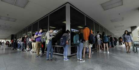 FILE - In this March 6, 2018 file photo, a line of mostly students wait to vote at a Texas primary election polling site on the University of Texas campus in Austin, Texas. The ACLU and other groups slammed Texas elections officials who say they found 95,000 people identified as non-citizens who had a matching voter registration record. Texas Attorney General Ken Paxton now says many of them could have become citizens and voted legally.(AP Photo/Eric Gay, File)