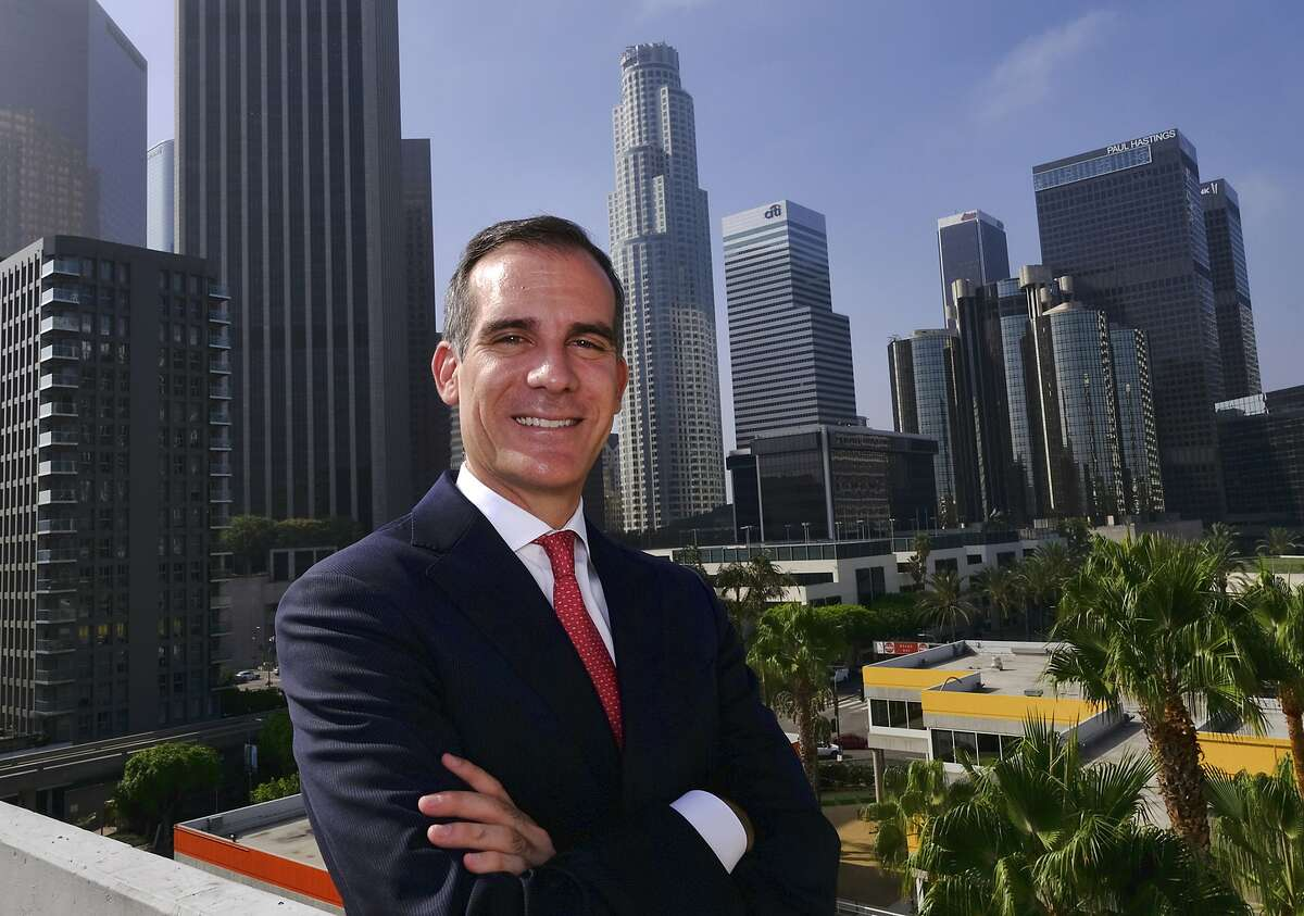 FILE - In this Aug. 23, 2018, file photo Los Angeles Mayor Eric Garcetti poses in front of a sprawling downtown Los Angeles landscape. Garcetti said Monday, Jan. 28, 2019, that homicide is down 8.2 percent, rape is down 12.4 percent, gang crimes are down 8 percent and property crime is down 2 percent. He said the number of homicides is at its second lowest in more than 50 years. (AP Photo/Richard Vogel, File)