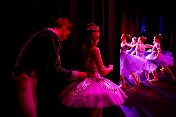 Dancer Joshua Webb ties Grace Rosendin's tutu right before she gets on stage during the final performance of the Nutcracker at the State Street Theater in Oroville, California on Sunday January 20, 2019. Grace lost her home in Paradise during the Camp Fire. The ballet school was also destroyed.
