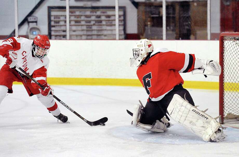 At left, Julian Ribushofski (#19) of Greenwich shoots the puck that beat Fairfield Combined goalie Will Capalbo (#30) for a goal during the boys high school ice hockey game between Fairfield Warde/Ludlowe combined teams and Greenwich High Schools at Hamill Rink in Greenwich, Conn., Thursday, Feb. 15, 2018. Photo: Bob Luckey Jr. / Hearst Connecticut Media / Greenwich Time