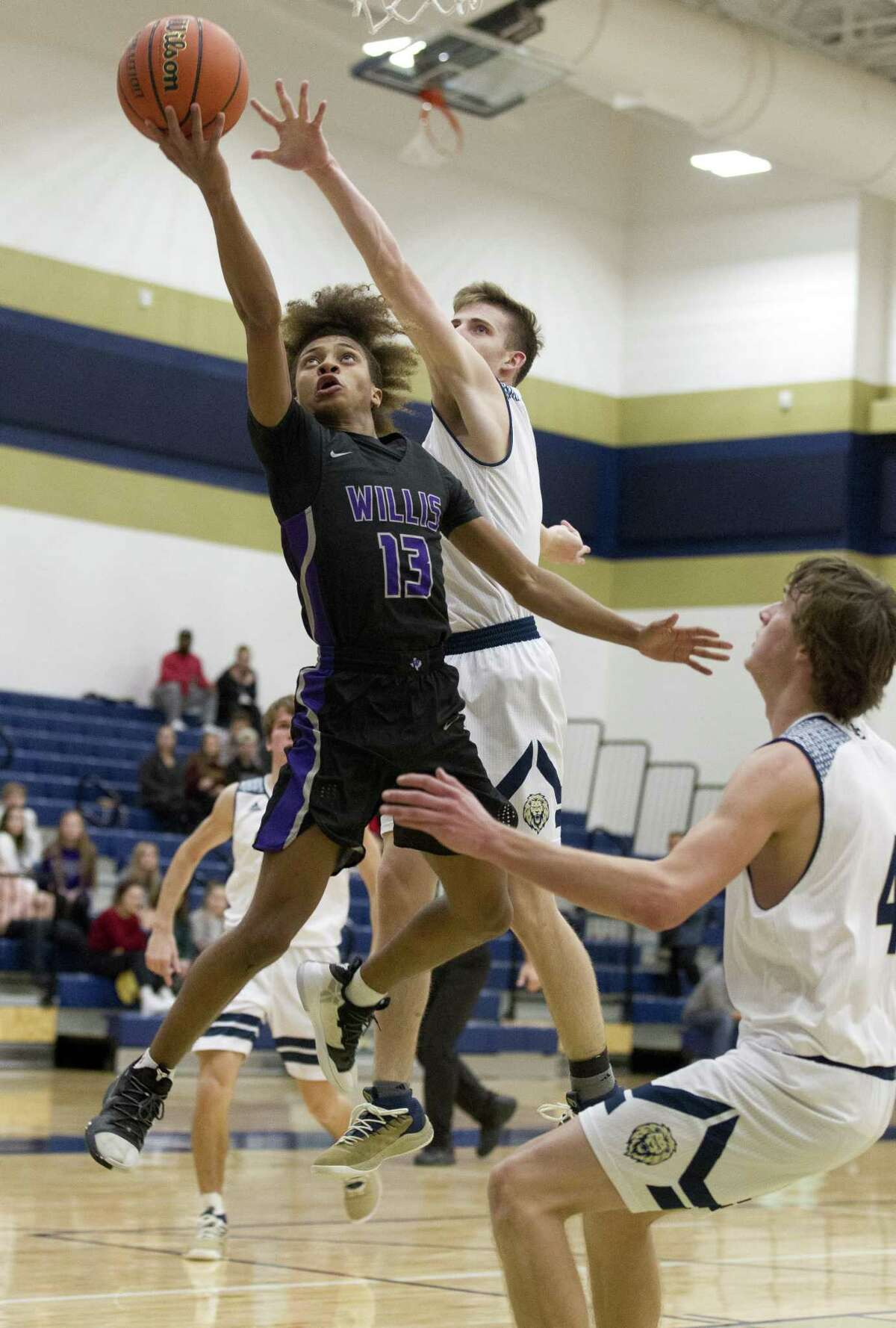 Willis point guard D'Shawn Woods (13) makes a shot past Lake Creek point guard Pierce Spencer (5) during the third quarter of a District 20-5A high school basketball game, Tuesday, Jan 29, 2019, in Montgomery.