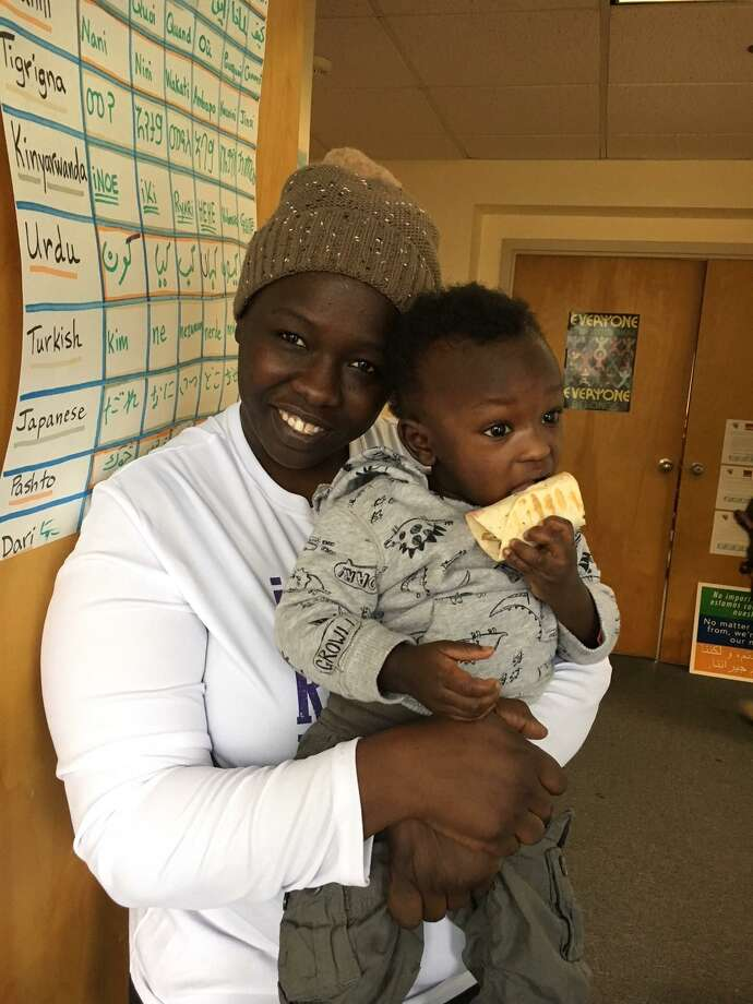 Ashar Ahmad, who is from  Sudan, holds her toddler, Kutti, at IRIS offices. Ahmad will be helping with the 5K fund-raising race on Sunday. Photo: Contributed Photo
