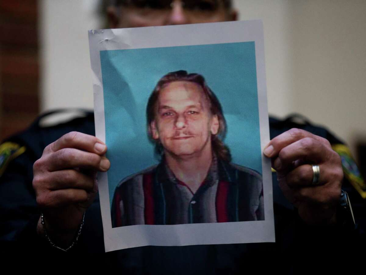 A Houston Police officer holds up the photo of one of the suspects , 59-year-old Dennis Tuttle, during a press conference at Memorial Hermann Hospital, which provided updates on the officers recovering from lasting night's drug search warrant Tuesday, Jan. 29, 2019, in Houston. Four officers were shot and one was injured during the warrant. The two suspects died.