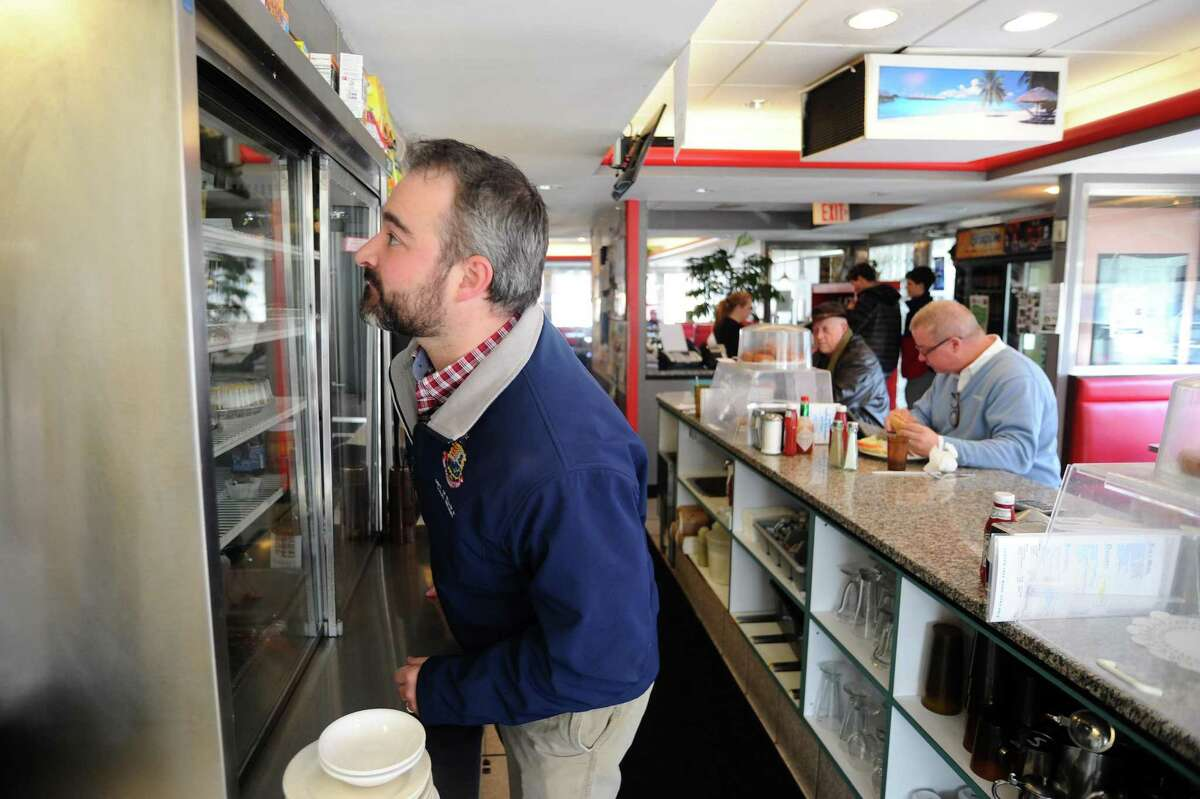 Stamford health inspector Timothy Noia checks the refrigerated cabinets of the Parkway Diner, making sure the food products are properly covered and at a safe temperature during an inspection in 2016.