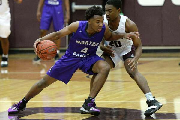 LJ Cryer (4) of Morton Ranch is guarded by Chris Ngene (20) of Cinco Ranch during the second half of a high school basketball game between the Cinco Ranch Cougars and the Morton Ranch Mavericks on Tuesday January 29, 2019 at Cinco Ranch HS, Katy, TX.