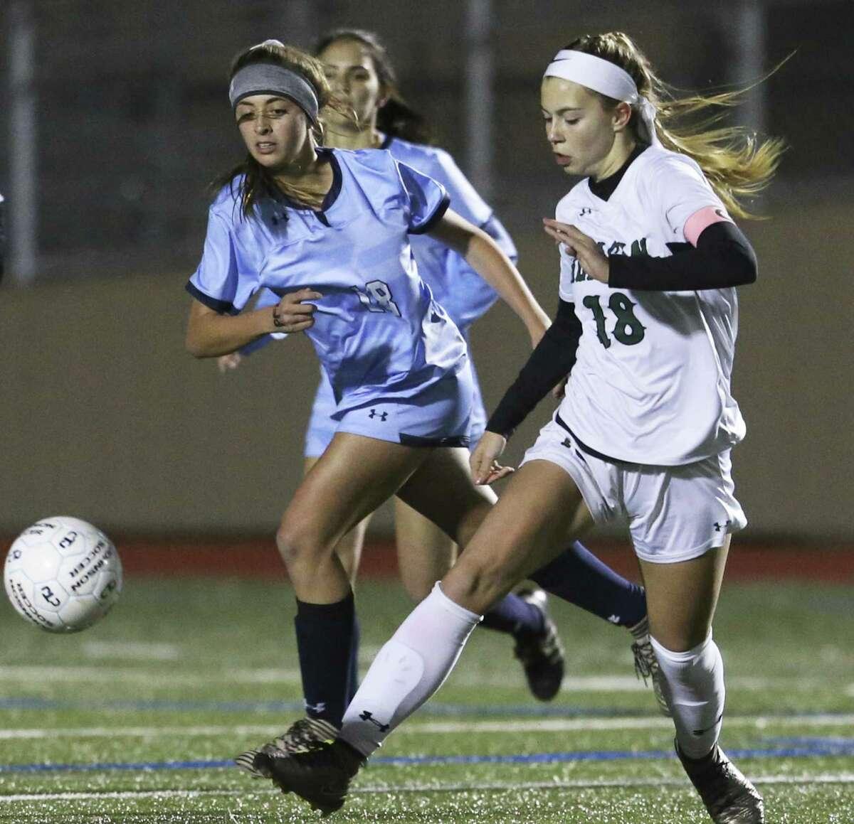 Reagan's Eden Jones kicks the ball away from Presley Drawe as Johnson plays Reagan in girls soccer at Comalander Stadium on January 29, 2019.