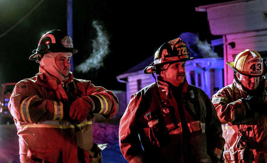 East Alton, Alton and Wood River fire crews work a fire Tuesday night at 210 Cooper Ave. in East Alton. Temperatures had dipped under 10 degrees. Photo: Nathan Woodside | The Telegraph