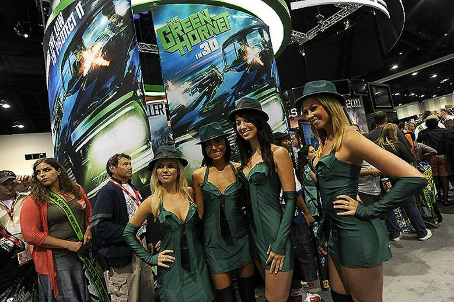 """Comic-Con attendees pose at """"The Green Hornet In 3D"""" stand during the Comic-Con 2010 preview night at San Diego Convention Center on July 21, 2010 in San Diego, California.  (Photo by Michael Buckner/Getty Images) Photo: Michael Buckner, Getty Images / 2010 Getty Images"""