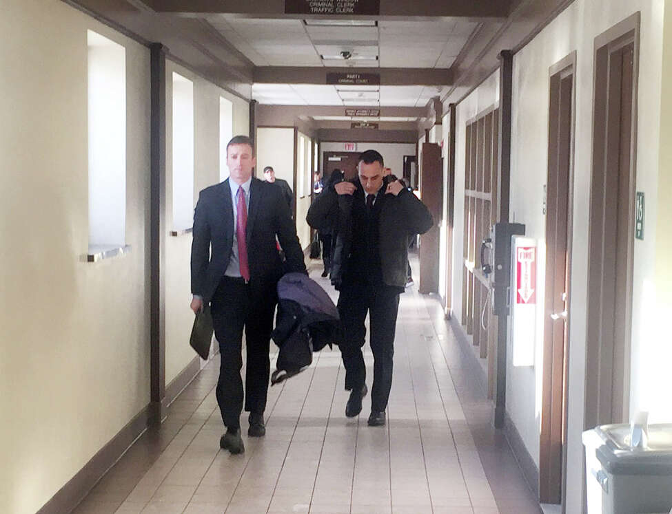 Albany police officer Christofer M. Kitto, right, leaves Utica City Court Wednesday after he was arraigned on a misdemeanor prostitution charge. Kitto was allegedly with a prostitute in Utica when he shot and killed a man who tried to rob him on Jan. 7. (Steve Hughes/Times Union)