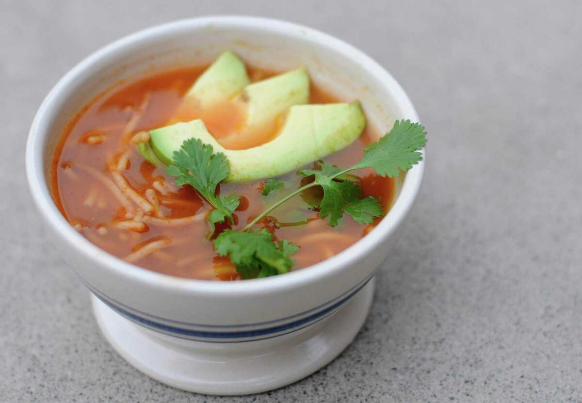 Sopa de Fideo, or Mexican-style noodle soup, garnished with avocado and cilantro