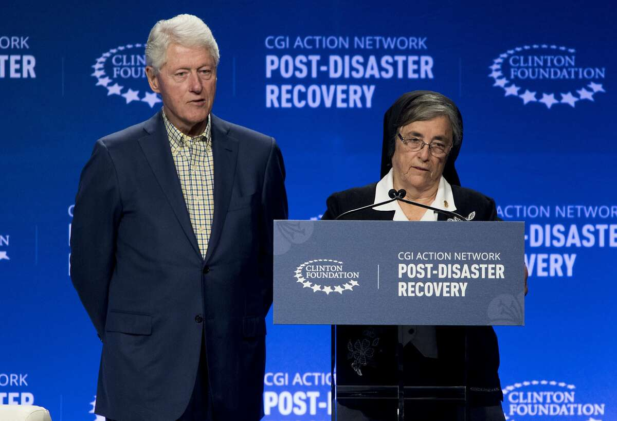 Former US President Bill Clinton gives recognition to Sister Rosemary Gonzalez, director of the Good Shepherd Home, for the work they carried out with people addicted to opiates after Hurricane Maria, during the third meeting of the Clinton Global Initiative (CGI) Action Network on Post-Disaster Recovery, held at the Miramar Convention Center, in San Juan, Puerto Rico, Tuesday Jan. 29, 2019. The Action Network brings together leaders in government, business, and civil society to develop strategies and solutions to address hurricane recovery needs. (AP Photo/Carlos Giusti)
