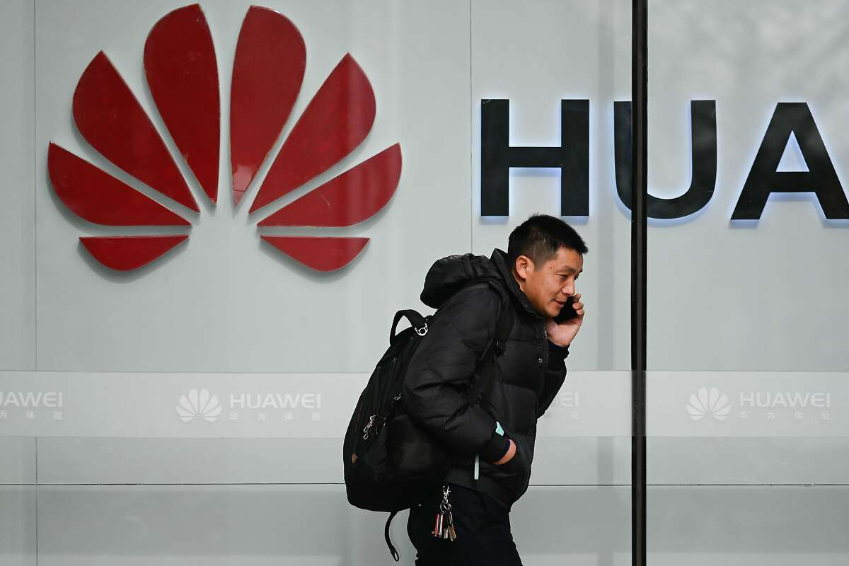 A pedestrian talks on his phone while he walking past a Huawei store in Beijing on January 30, 2019. - Fraud, obstruction of justice and cloak-and-dagger trade theft -- a US rap sheet alleging systematic skullduggery by Chinese telecom giant Huawei has deepened the company's problems just as it sought to win back global trust. (Photo by WANG ZHAO / AFP)WANG ZHAO/AFP/Getty Images