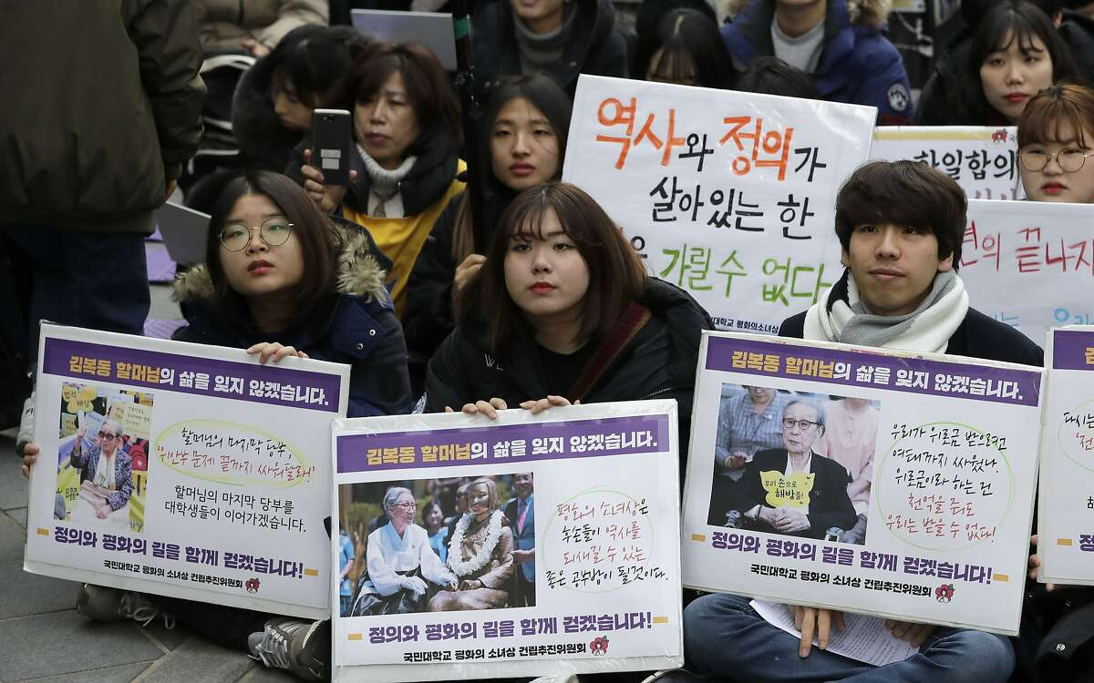 """Participants hold pictures of deceased Kim Bok-dong, one of former South Korean sex slaves who were forced to serve for the Japanese military in World War II, during a weekly rally near the Japanese Embassy in Seoul, South Korea, Wednesday, Jan. 30, 2019. Hundreds of South Koreans mourned the death of Kim during the rally demanded reparations from Tokyo over wartime atrocities. The banners read: """"We will never forget the life of Kim Bok-dong.""""(AP Photo/Lee Jin-man)"""