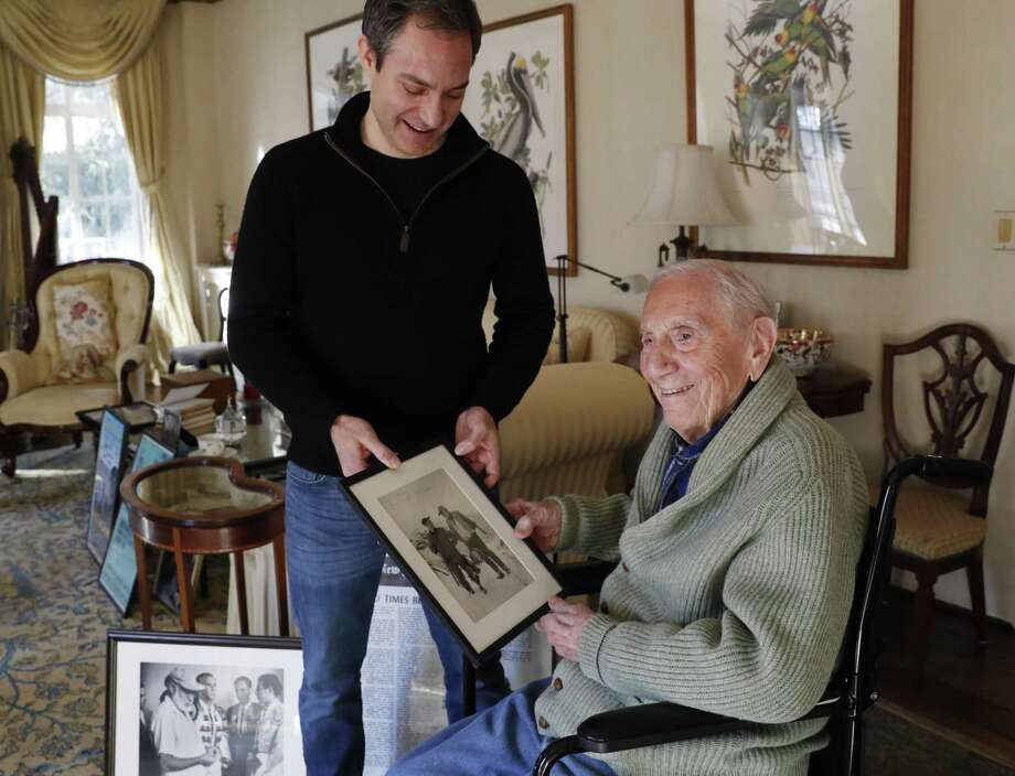 """Ernest Hemingway' s close friend and biographer A.E. Hotchner, right, looks through photographs of Hemingway and himself with son Tim Hotchner, a documentary filmmaker and writer, Tuesday, Jan. 22, 2019, at the family's home in Westport, Conn. When the 1958 film adaptation """"The Old Man and the Sea"""" hit theaters, Hemingway told the senior Hotchner that he hated it and urged his writer pal to do his own adaptation someday. Now 101, and with Tim's collaboration, Hotchner has finally completed Hemingway's request. Their stage adaptation of """"The Old Man and the Sea"""" is set to premiere in Pittsburgh on Feb. 1. (AP Photo/Kathy Willens) Photo: Kathy Willens / Associated Press / Copyright 2019 The Associated Press. All rights reserved"""