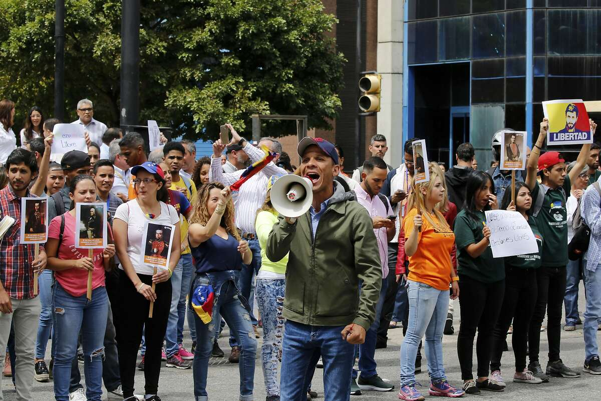 """Opposition lawmaker Gilbert Caro shouts """"Free elections"""" in a walk out against President Nicolas Maduro, in Caracas, Venezuela, Wednesday, Jan. 30, 2019. Venezuelans are exiting their homes and workplaces in a walkout organized by the opposition to demand that Maduro leave power. .(AP Photo/Fernando Llano)"""