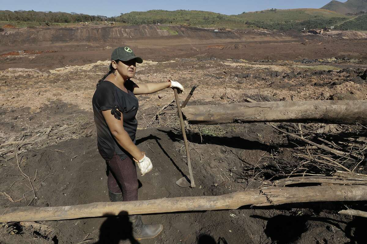 """Tereza Ferreira Nascimento pauses as she digs in search of the body of her missing brother Paulo Giovane Santos, with her garden tools, days after a dam collapse in Brumadinho, Brazil, Wednesday, Jan. 30, 2019. """"We are here since Friday taking turns between brothers, brothers-in-law, searching for the body so that we can at least give him a dignified burial,"""" said Nascimento, holding back tears. """"So far it has been in vain."""" (AP Photo/Andre Penner)"""