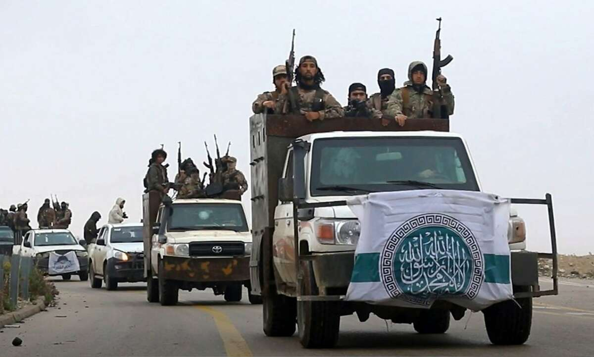 This photo released Dec. 4, 2018 by the al-Qaida-affiliated Ibaa News Agency, shows al-Qaida-linked fighters driving their vehicles during a military drill in northern Syria. It took the al-Qaida-linked militants only few days to capture more than two dozen towns and villages in and around Idlib province, cementing the group's control over an area in northwestern Syria the size of neighboring Lebanon. The push by members of Hayat Tahrir al-Sham, or HTS, is the most serious blow to a September cease-fire for Idlib brokered by Russia and Turkey, and puts tens of thousands of civilians at risk of losing medical support due to a drop in aid from western agencies. (Ibaa News Agency, via AP)