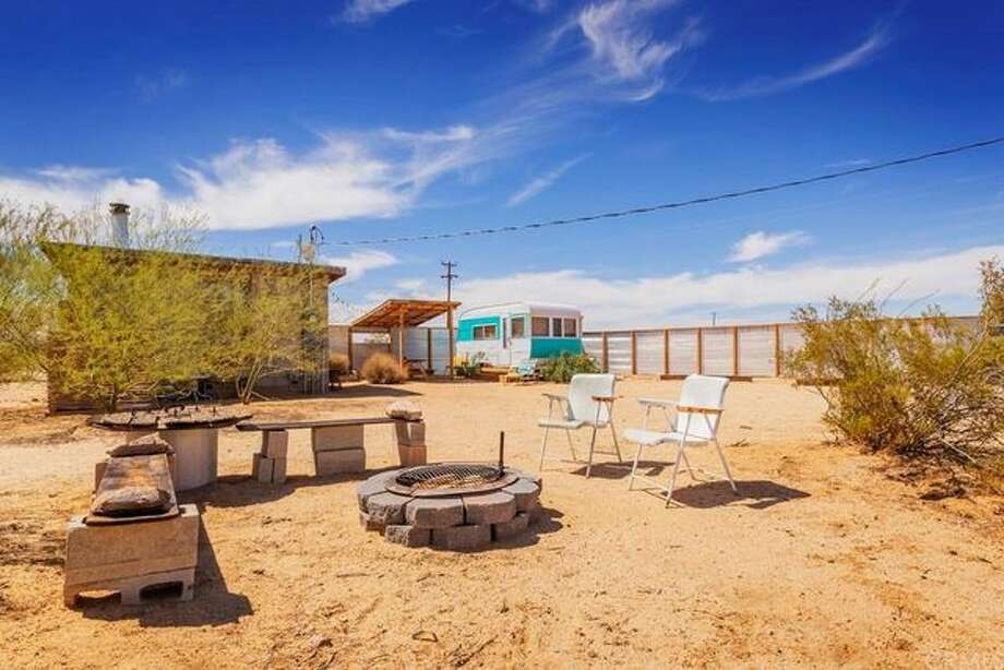 This tiny cabin nestled into the desert landscape of Joshua Tree, Calif. is now on the market for $199,000. The property comes with 5 acres plus other structures. Photo: Realtor.com