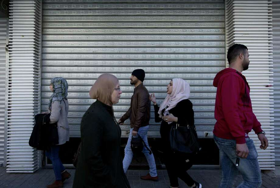 Palestinians walk past a closed shop in the West Bank city of Ramallah last week. Photo: Associated Press / Copyright 2018 The Associated Press. All rights reserved