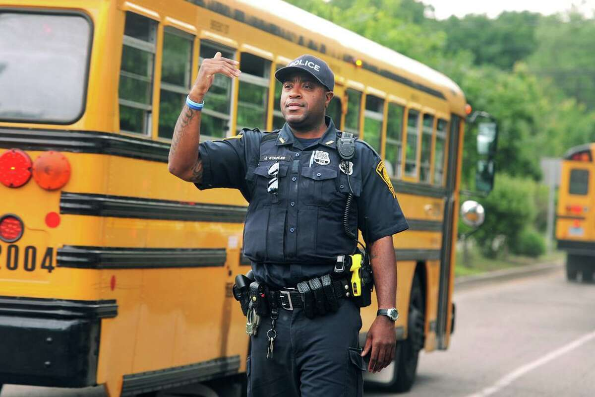 Bridgeport Police Officer John Staples, a Schools Resource Officer (SRO), directs traffic as school buses leave Central High School at the end of the day in Bridgeport, Conn. June 15, 2018.
