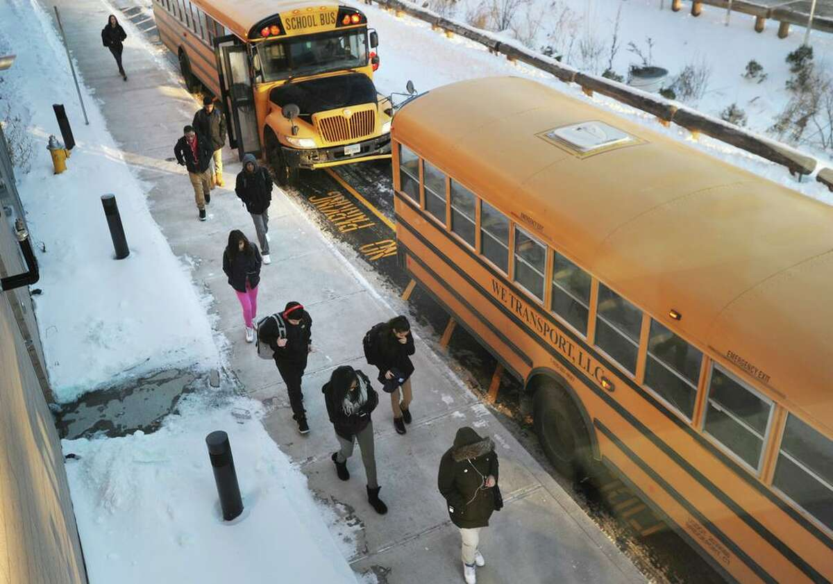 Buses arrive at the start of the school day at the Fairchild Wheeler Interdistrict Magnet School in Bridgeport, Conn. on Thursday, January 29, 2015.