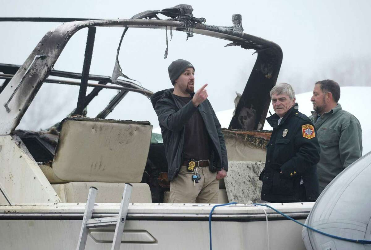 Norwalk Police and Fire Department investigators speak with the owner as they examine a power boat stored at Cove Marina on Jan. 8.