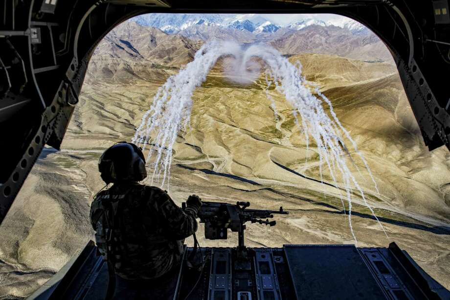 A U.S. Army crew chief observes a flare test during a training flight in Afghanistan, March 14. A hasty American withdrawal from Afghanistan, experts said, would erode the authority and legitimacy of the Afghan government, raising the risk that the Taliban could recapture control. Seventeen years of fighting there, and the question remains whether those circumstances will ever change. Photo: TECH. SGT. GREGORY BROOK /NYT / U.S. AIR FORCE