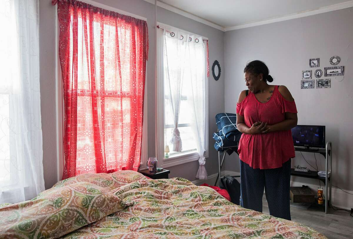 Regina Daniels stands inside the double room she shares with Terrence Daniels at The Holland, a transitional homeless-to-housing pipeline facility in Oakland, Calif. Tuesday, Jan. 29, 2019.