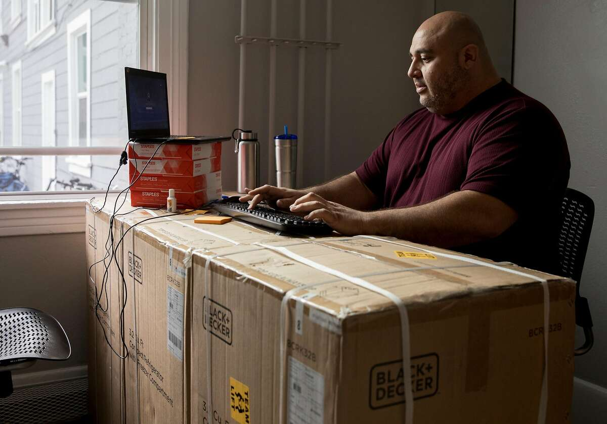 Facility manager Christian Munoz uses a desk made from mini refrigerator boxes while working in his office at The Holland, a transitional homeless-to-housing pipeline facility in Oakland, Calif. Tuesday, Jan. 29, 2019.