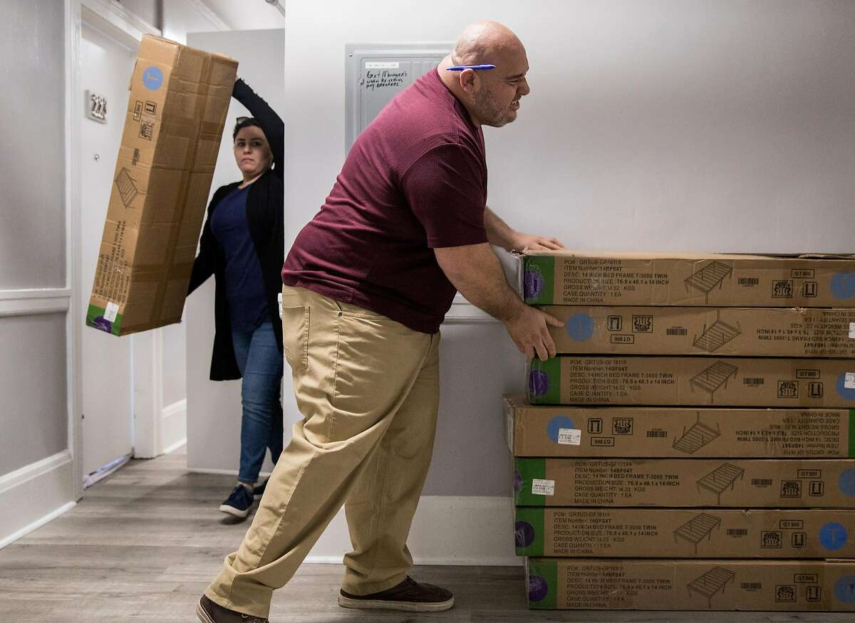 Facility manager Christian Munoz helps a fellow employee move empty boxes from a storage closet inside The Holland, a transitional homeless-to-housing pipeline facility in Oakland, Calif. Tuesday, Jan. 29, 2019.