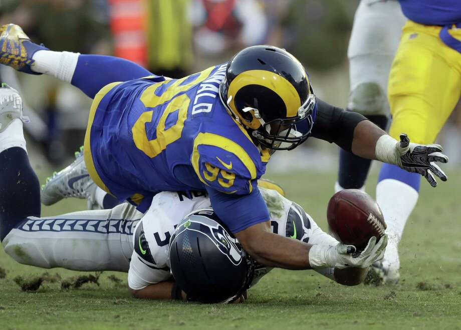 In this Nov. 11, 2018, file photo, Seattle Seahawks quarterback Russell Wilson (3) battles Los Angeles Rams defensive end Aaron Donald (93) for a ball Wilson lost on a fumble and returned for a touchdown by defensive end Dante Fowler during the second half in an NFL football game in Los Angeles. Photo: Alex Gallardo, FRE / Associated Press / Copyright 2018 The Associated Press. All rights reserved