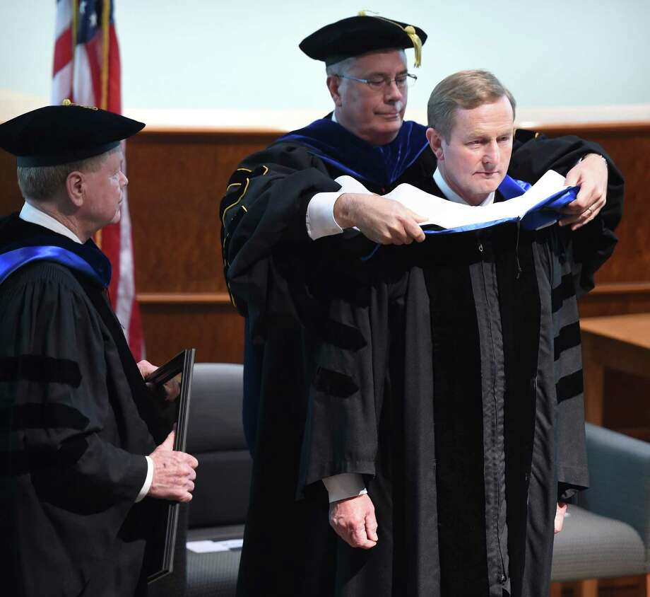 (Arnold Gold-New Haven Register) Enda Kenny, Taoiseach of Ireland, is hooded by Quinnipiac University Provost Mark Thompson during a ceremony in the university's Center for Communications and Engineering in Hamden on 9/24/2015. At left is Quinnipiac University Trustee Hugh Keefe