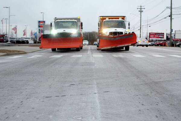 Two plows wait at the stop light along Boston Post Road at High Street in Milford, Conn., on Wednesday, Jan. 30, 2019. A dusting of snow fell in the area with temperatures falling to 5 degrees overnight.