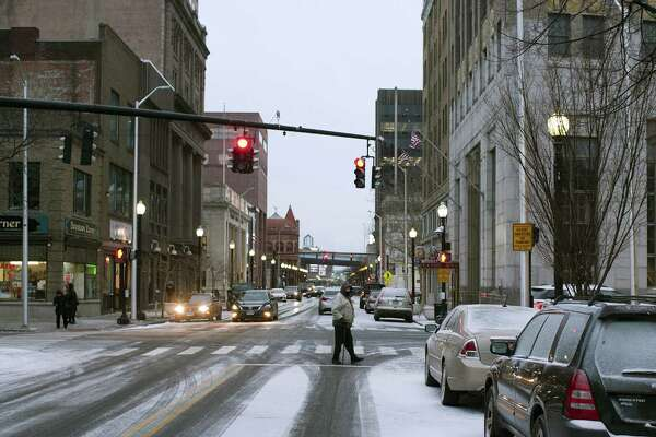 FILE PHOTO - Pedestrians make their way along Main Street in downtown Bridgeport, Conn., on Wednesday, Jan. 30, 2019. A dusting of snow fell in the area with temperatures falling to 5 degrees overnight.