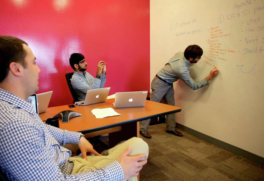 The MassChallenge marketing team, from left, Jeff Danford, Jibran Malek and Robby Bitting, test a new app from IdeaPaint. Photo: Wendy Maeda/Globe Staff, Globe Staff / The Boston Globe / The Boston Globe