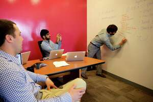 The MassChallenge marketing team, from left, Jeff Danford, Jibran Malek and Robby Bitting ,test a new app from IdeaPaint. MassChallenge is Houston's newest business accelerator program.
