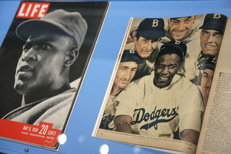 "In this Tuesday, Jan. 29, 2019 photo, news articles about Brooklyn Dodgers baseball player Jackie Robinson are displayed at the exhibit ""In the Dugout with Jackie Robinson: An Intimate Portrait of a Baseball Legend"" at the Museum of City of New York in New York. The 100th anniversary of Robinson's birth is celebrated Thursday, Jan. 31, with the opening of the exhibit. (AP Photo/Seth Wenig) Photo: Seth Wenig / Associated Press"